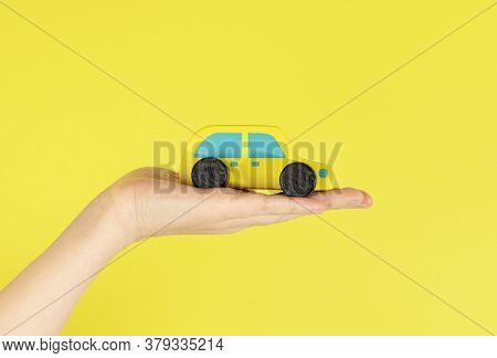 Yellow Toy Car In A Womans Hand, Isolated Against A Yellow Background