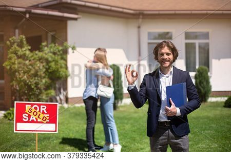 Smiling Realtor Showing Okay Gesture And Millennial Couple Embracing Near Their New Property, Copy S