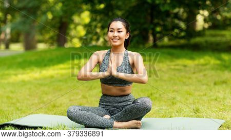 Calm Asian Girl Meditating In Lotus Pose During Her Yoga Class Outdoors. Panorama