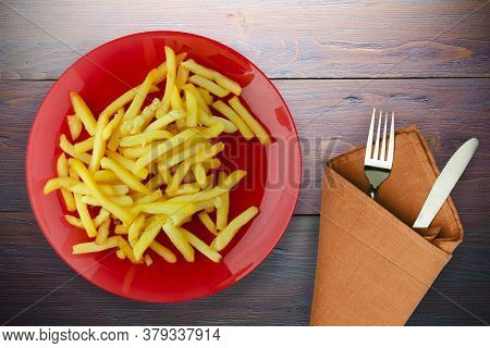 Fry Potatoes On A Wooden Background. Fry Potatoes On Red Plate With Fork And Knife Top View