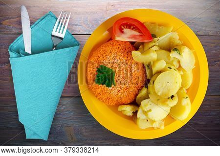 Meatball With Potatoes On Purple Wooden Background. Meatball With A Slice Of Tomato On Yellow Plate