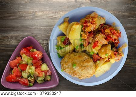 Cutlets With Potatoes And Stewed Tomatoes. Cutlet On Light Blue Plate With Vegetable Salad On Black
