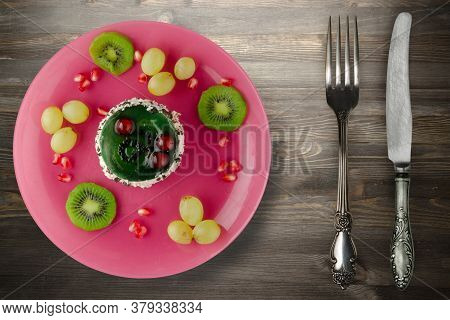 Dessert Of Cake And Fruit Grapes, Kiwi, Pomegranate On A Black Wooden Background. Dessert With Fruit