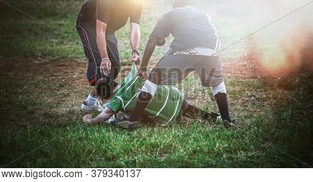 young man savagely beaten in a park at sunset by the members of a neighborhood gang