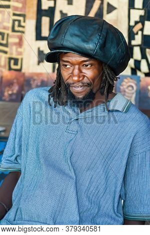 Happy Rasta man with dread locks and leather hat, in front of a  traditional African blanket