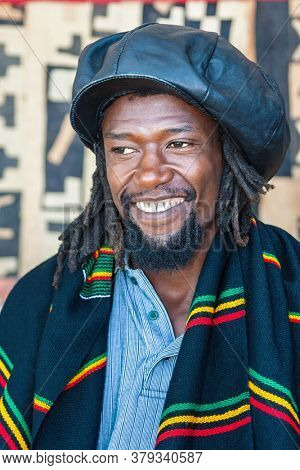 Happy Rasta man with dread locks and leather hat, wrapped in a  traditional African blanket