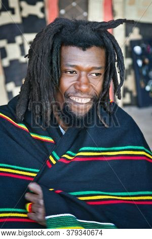 Happy Rasta man with dread locks wrapped in a  traditional African blanket
