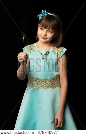 Little Girl Holding Firewors On Black Background