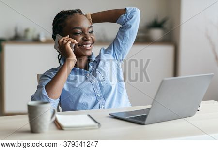 Break At Work. Happy Black Female Entrepreneur Talking On Cellphone, Relaxing At Workplace In Office