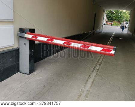 Red Automatic Barrier Restricting The Entrance To The Arch Of A Residential Building. Restriction Of