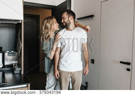Photo of a young optimistic loving couple standing together indoors at home