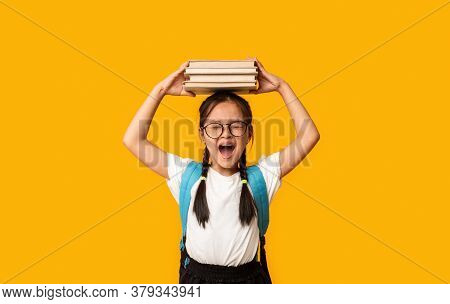 Discontented Japanese School Girl Shouting Holding Books On Head Standing Over Yellow Background. Ba