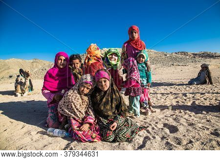 Hurghada, Egypt- Feb 4 , 2020: Young children sit on the sand in the desert near Hurghada, Egypt.