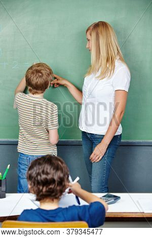 A student solves a math problem on the blackboard in elementary school
