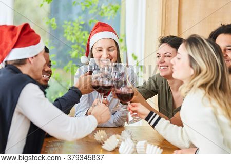 Friends celebrate Christmas party between Santa Claus and Christmas with a glass of red wine at home