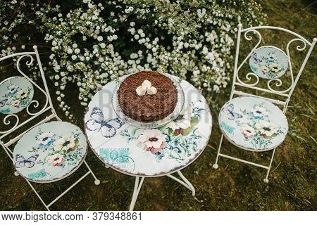 Garden Furniture With Floral Details. Chocolate Cake With Forgotten Kisses On Top. Floral Details
