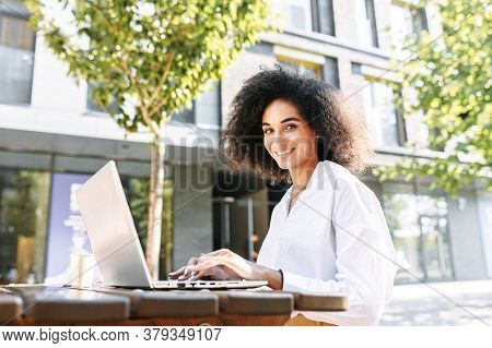 Beautiful African-american Businesswoman Using Laptop Computer For Work Remotely Outdoors. A Smiling