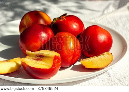 Red Ripe Organic Nectarine Fruits On The White Plate On Nature Background. Summertime Healthy Eating