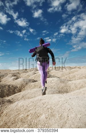 Woman Solo Tourist Running In Jump, Rear View On Hill Area In Sportswear And With Backpack Looking I