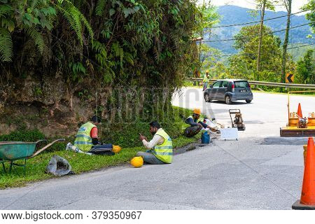 Road Repair In Asia. Fenced Road Section With A Pit. Workers In Overalls Are Resting On The Sideline
