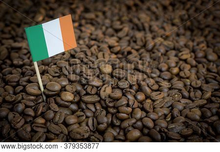 Irish Flag Sticking In Roasted Coffee Beans. The Concept Of Export And Import Of Coffee