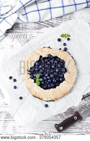 Shortbread Galette With Bilberry On The Baking Parchment On The White Wooden Table. Top View