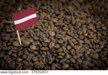 Latvia Flag Sticking In Roasted Coffee Beans. The Concept Of Export And Import Of Coffee