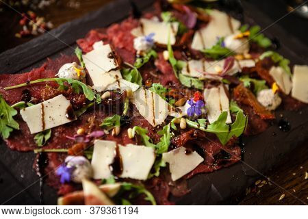 Beef carpaccio with pepper, rucola and parmesan served on a board. Delicious healthy Italian traditional antipasti snacks food closeup served for lunch with wine in modern gourmet cuisine restaurant.