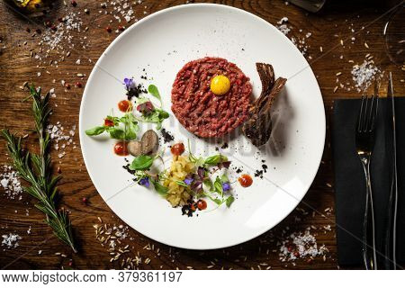 Steak tartare. Horseradish creme, black bread, baguette chips on white plate. Delicious healthy raw meat food closeup served on a table for lunch in modern cuisine gourmet restaurant