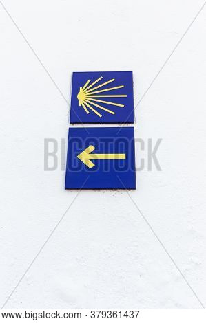 Camino De Santiago Yellow Scallop And Arrow Sign On White Wall. Way Of St. James Signs Pilgrimage To