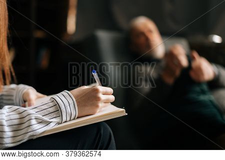 Close-up Of Woman Psychologist Taking Notes In Notebook, Mature Man Patient Answering Questions In O