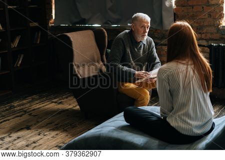 Mature Man Psychologist Consulting Female Patient At Psychological Appointment In Dark Home Office.