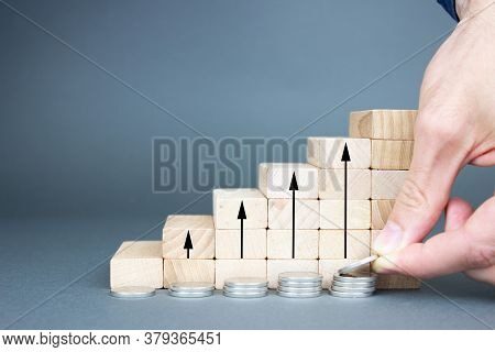 A Man's Hand Folds Coins Near Wooden Blocks In The Form Of A Ladder With Upward Arrows. The Concept