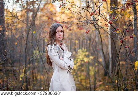 Sad, Pensive Girl In A Raincoat In The Autumn Forest At Sunset. Warm Light. Yellow And Red Foliage