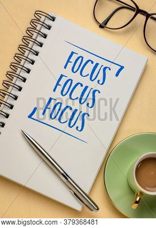 Focus concept - handwriting in a spiral notebook with a cup of espresso coffee, business, productivity and prioritizing
