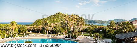 Mediterranean Landscape. Water Pool with Sunbeds and Umbrellas. Luxury Panoramic View on Mediterranean Sea. Sardinia. Italy.