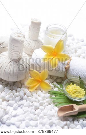 Spa setting with green palm leaves , herbal ball, frangipani,salt in bowl ,candle , herbal ,ball ,spoon on pile of white stones