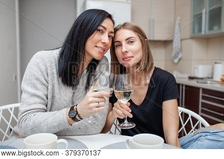 Friends Meeting With Wine And Cake In The Modern Style Kitchen. Young Women Smile And Joke With Glas