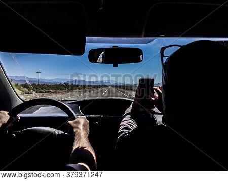 Back View Inside Car Shot Driver And Copilot Driving At Empty Arid Higway, San Juan Province, Argent
