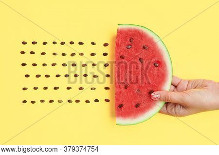 Watermelon Slice With Seeds In Hands On Yellow Background. Food Art. Flat Lay