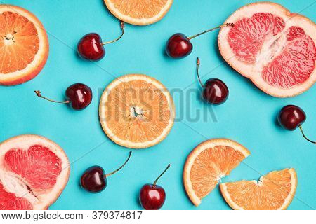 Summer Tropical Fruits On Blue Background. Mix Of Grapefruit, Orange And Cherry. Food Concept. Flat