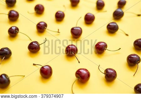 Fresh Cherry On Yellow Background. Colourful Bright Pattern