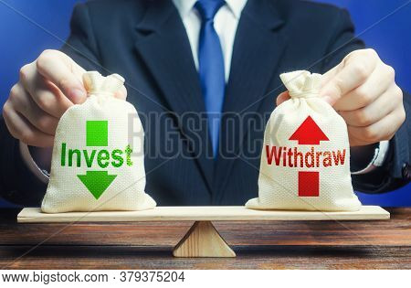Businessman Holds Bags Invest And Withdraw On Scales. Business Profit Management. Investment In A Co
