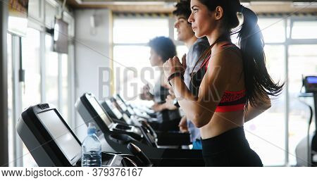Group Of Young People Exercising On A Treadmill At Gym