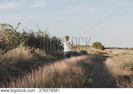 Adorable Little Girl Running Down The Hill Back View. Happy Child Running In Wild Grass Countryside