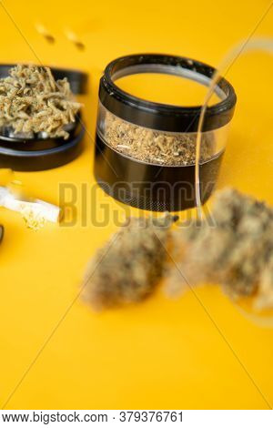 Joint Weed. Sativa Thc Cbd. Marijuana Weed Bud And Grinder. Yellow Background.