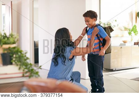 Mother Saying Goodbye To Son As He Leaves Home For School
