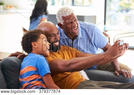 Multi-Generation Male African American Family On Sofa At Home Posing For Selfie On Mobile Phone