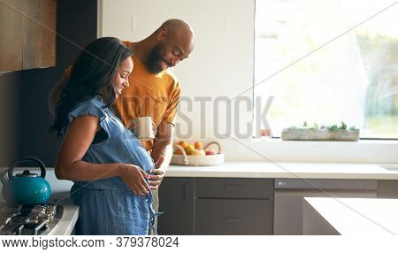 Loving African American Husband With Pregnant Wife At Home In Kitchen Together