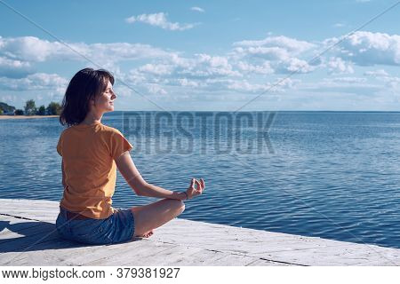 Side View Of A Young Pretty Woman Enjoy Sea View Sitting On A Wooden Seafront In Lotus Position